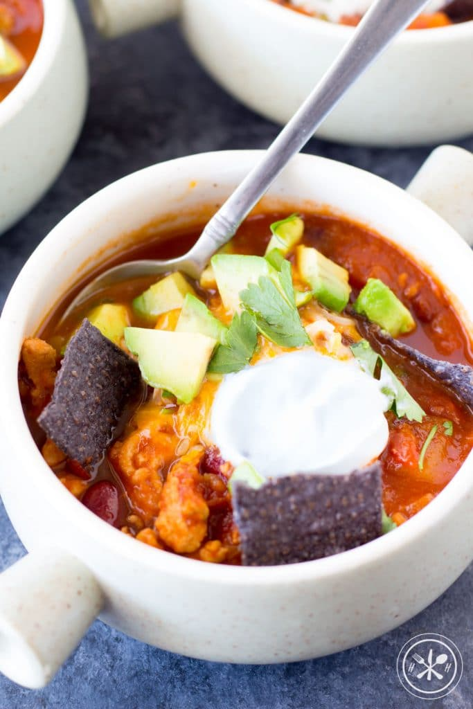 Turkey chili in a bowl with cream and chips.