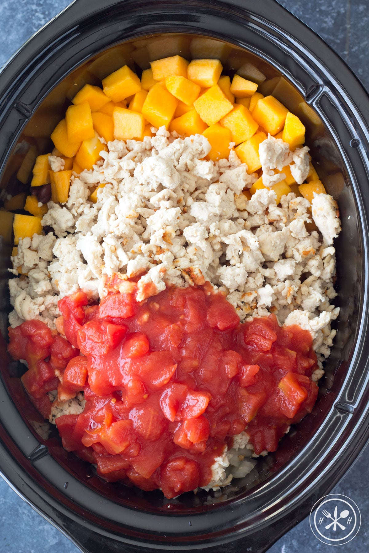 Slow cooker with chili ingredients added to it. Turkey, butternut squash, and tomatoes