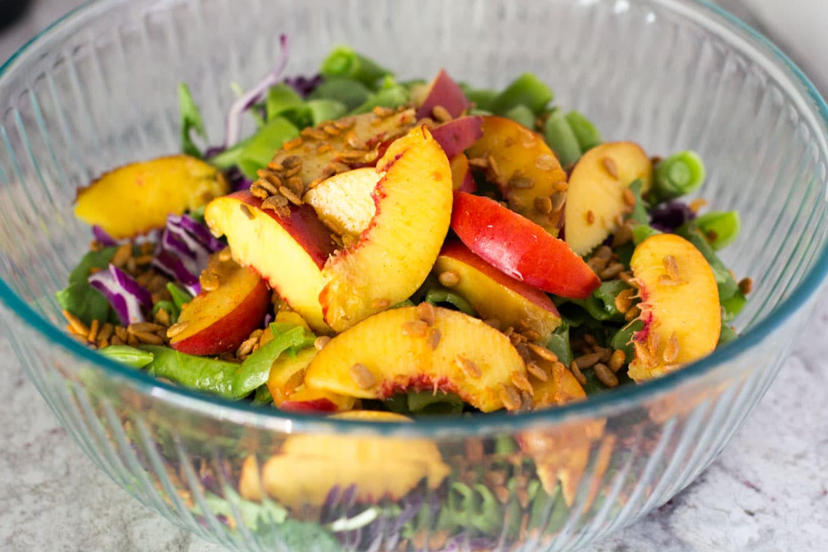 Salad with nectarines, snap peas, cabbage, and ginger sesame dressing