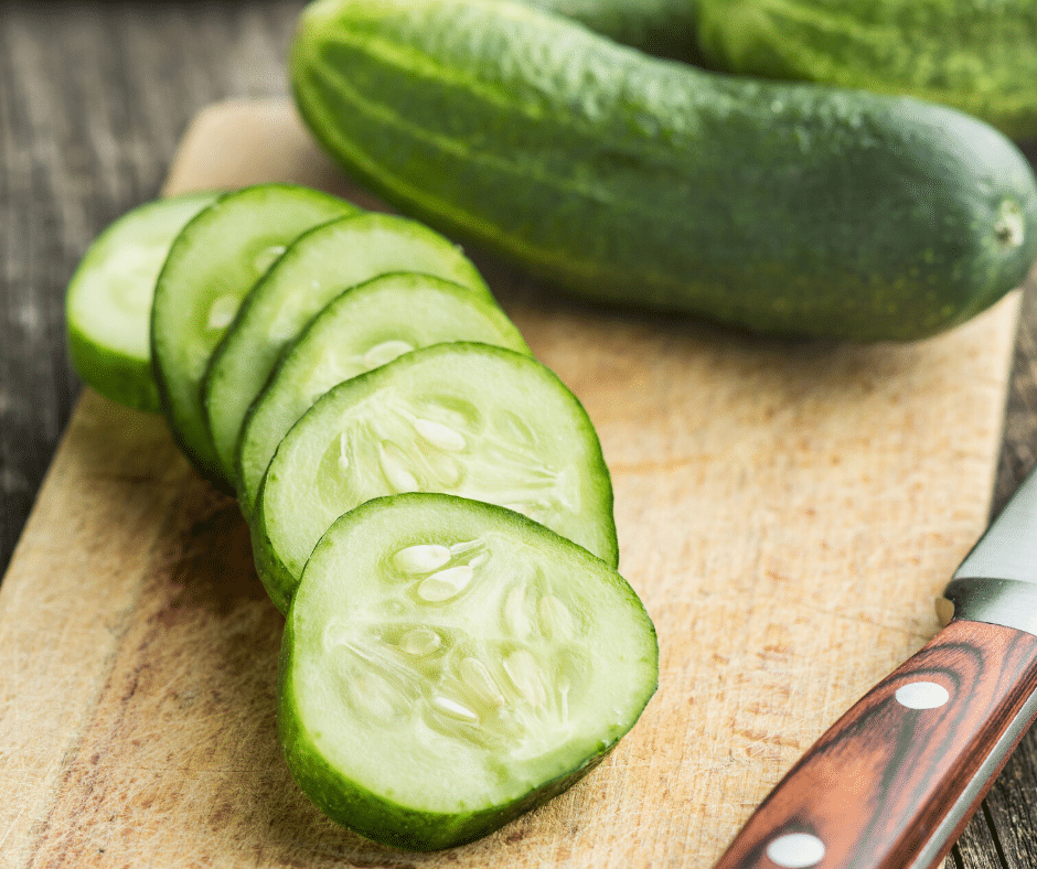 cucumbers on cutting board with a knife