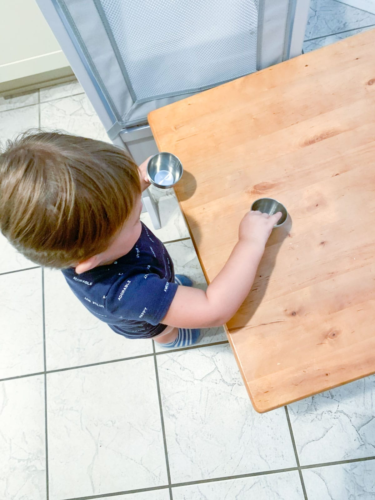 toddler paying with cups
