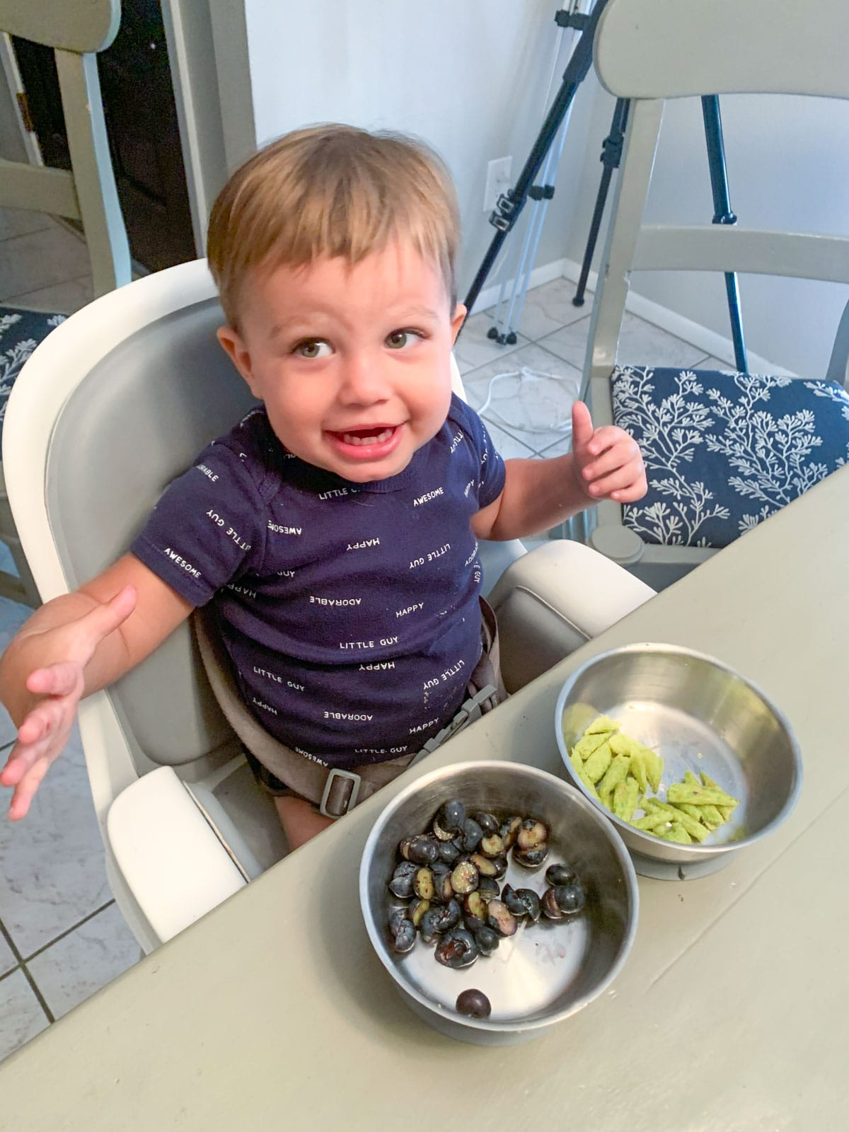 toddler having snack of blueberries and snap peas