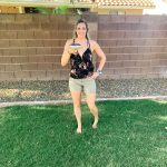 girl standing in backyard with amargarita glass black tank top and baeigh short