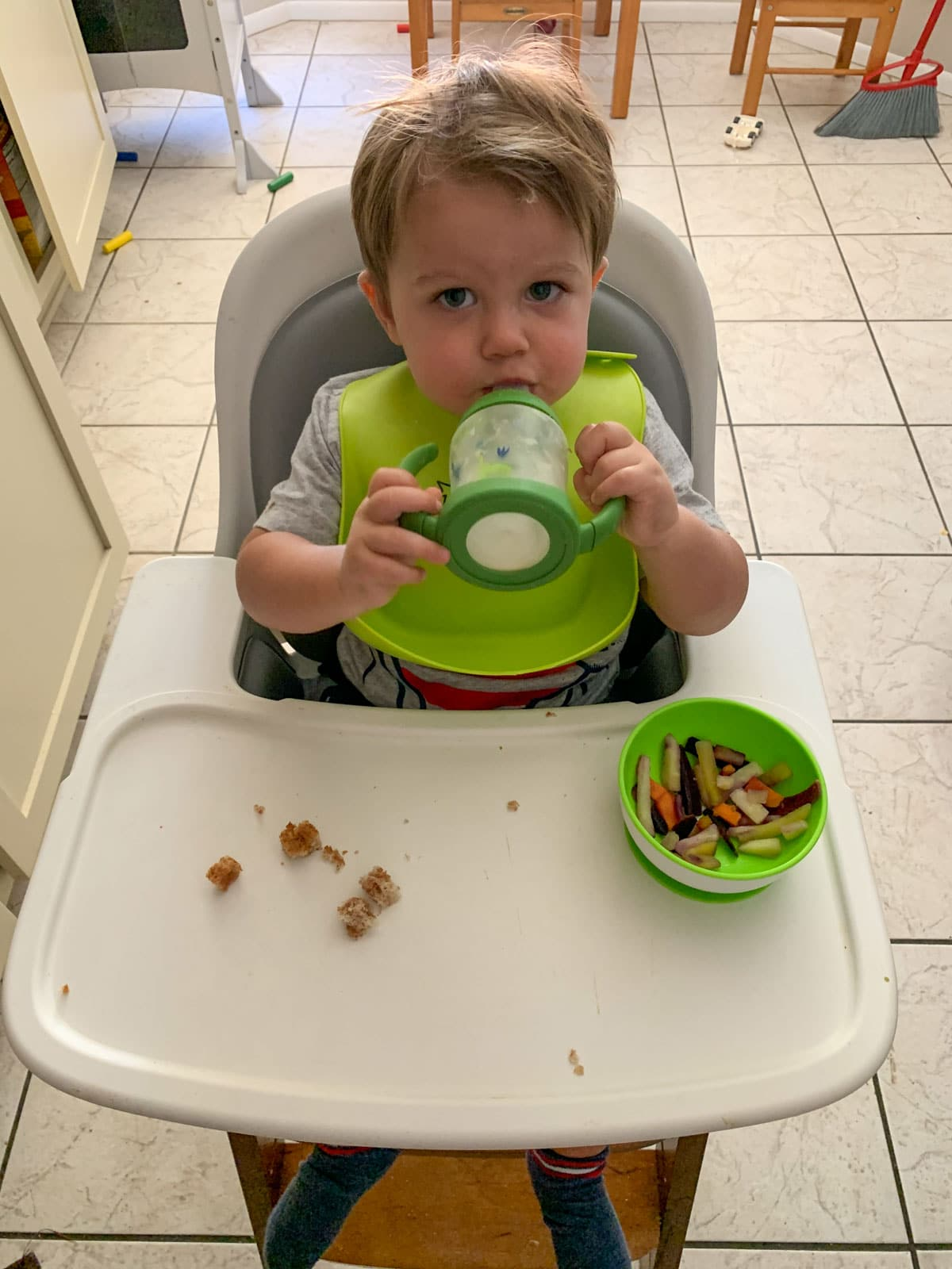 toddler drinking milk and eating veggie mix in a bowl with peanut butter and jelly
