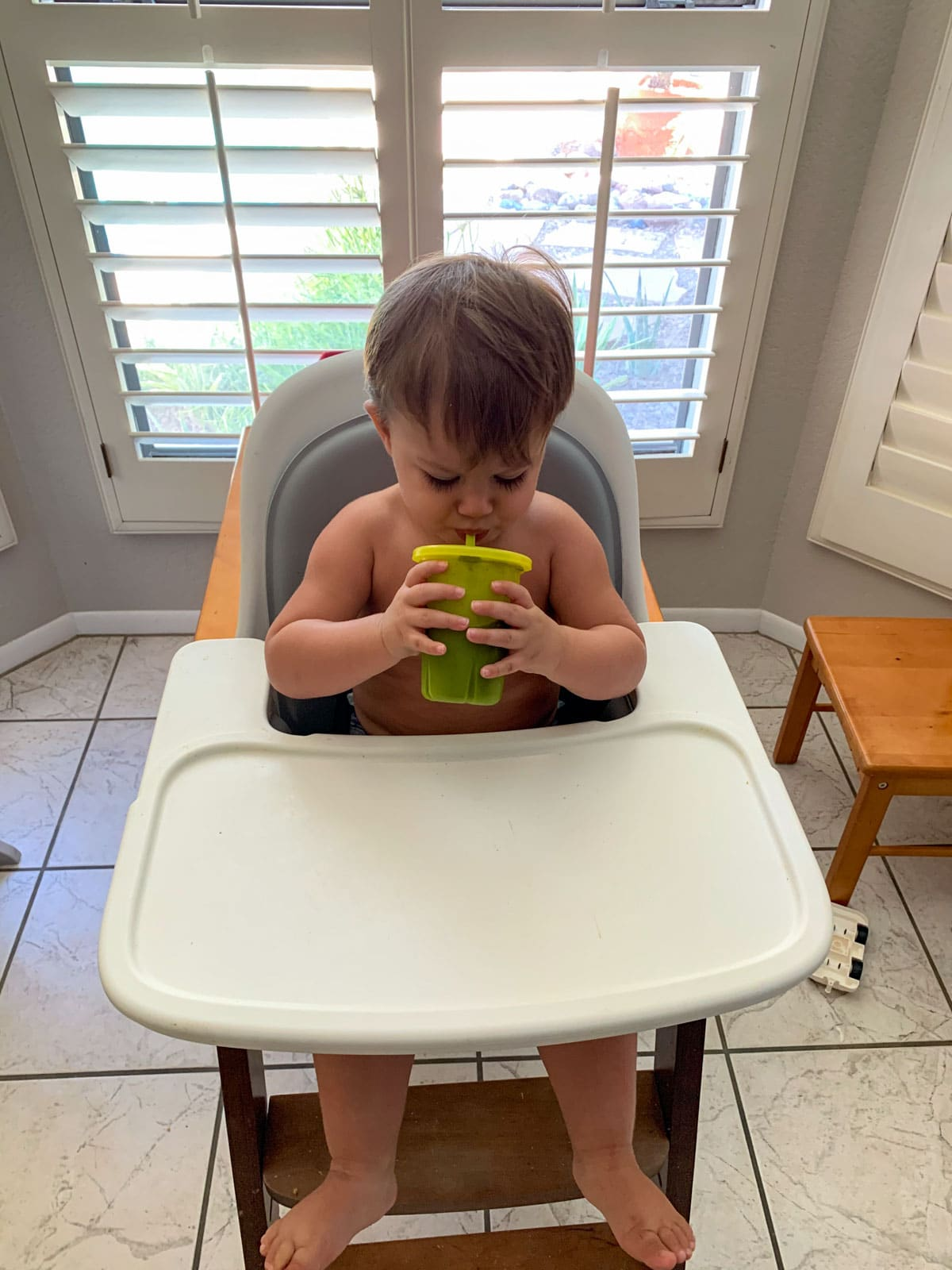 toddler drinking a smoothie in his high chair