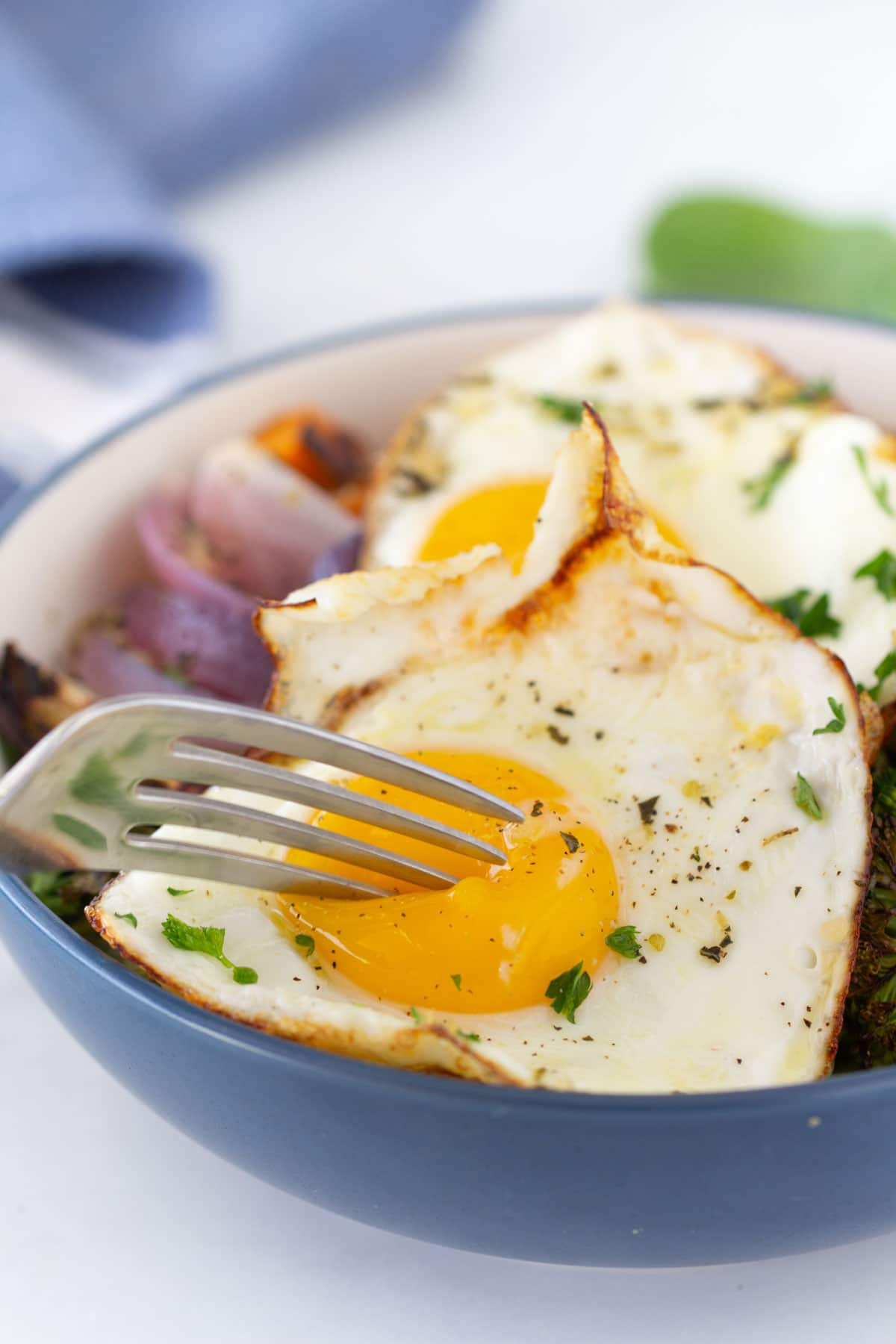 fried eggs on top of roasted veggies with fork cutting through